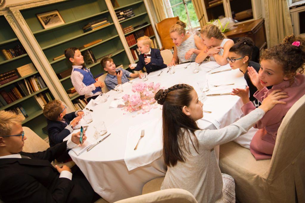 De kinderen zitten allemaal aan de tafel bij de communicant en zijn gezellig met elkaar aan het babbelen