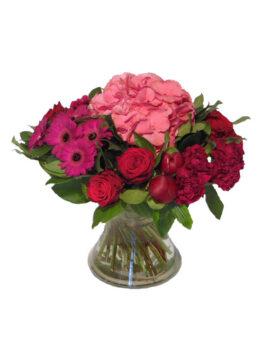 Een boeket bloemen in een vaas met Hortensia en pioenen en enkele grote gerbera's.
