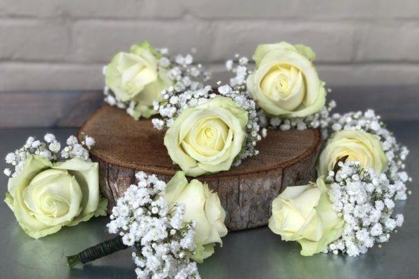 Eenvoudig mooie corsages met een avalanche roos en gipskruid.