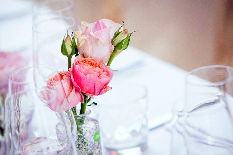 De tafel wordt versierd met een vaasje gevuld met enkele roosjes voor een communiefeest
