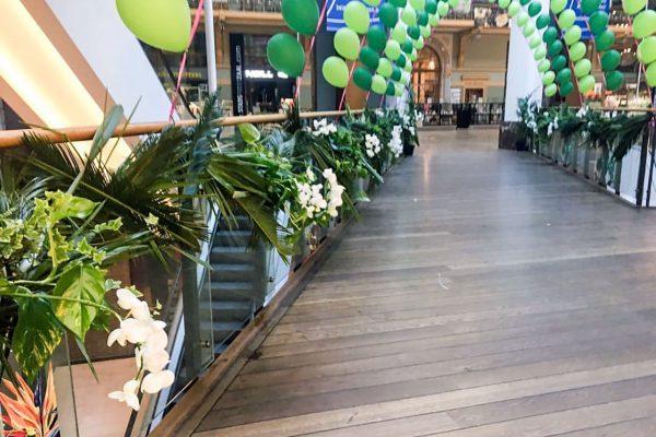 Een urban jungle slinger van groene junelbladeren met orchideeën versieren de wandelbrug in de Stadsfeestzaal in Antwerpen